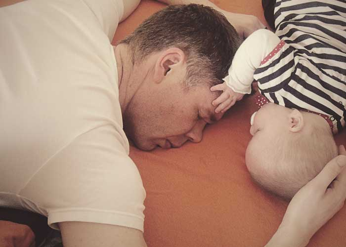 dad sleeping next to a baby