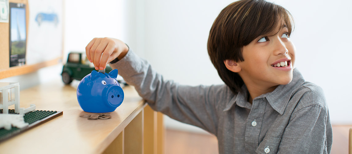 Young boy putting coins into a piggy bank