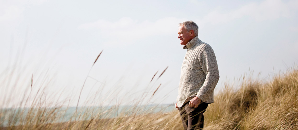 Retired man looking out to sea on a sunny day