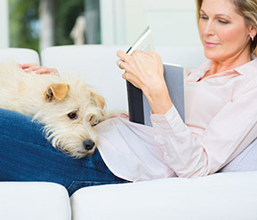 A lady reading a book with her pet dog