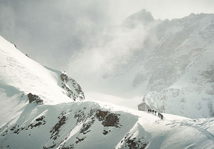A group of hikers climb a snowy mountain